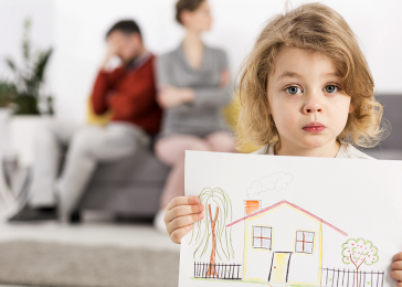 child holding drawing of home with parents fighting in background