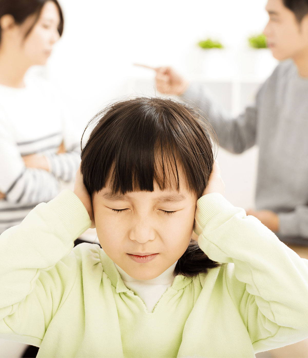 child covering ears as parents fight