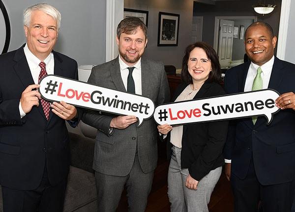 spooner attorneys holding #lovegwinnett and #lovesuwanee signs